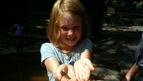 young girl holding a crayfish