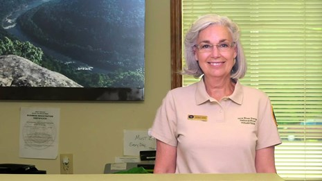 volunteer behind a visitor center desk