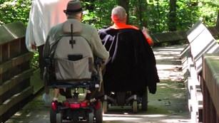 visitors in wheel chairs on boardwalk trail