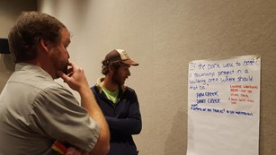 park ranger and community member looking at flip chart