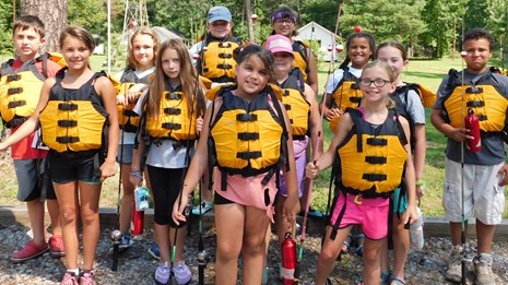 kids with life jackets preparing for a river trip