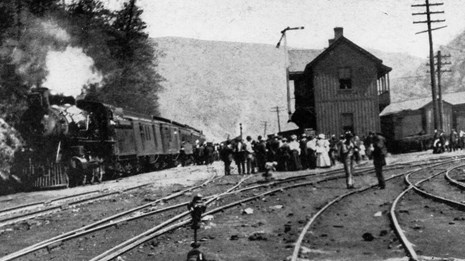 historic black and white photo of railroad depot with train