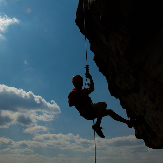 rock climber silhouetted on cliff