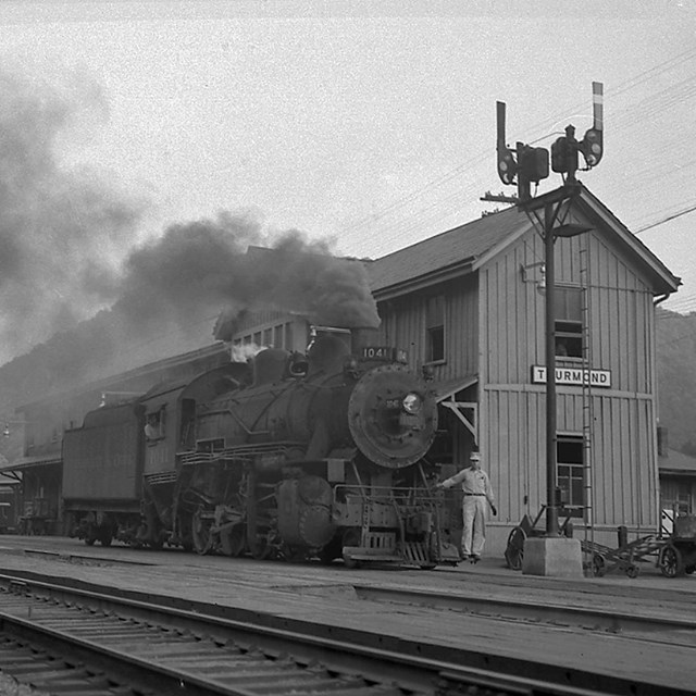black and white photo of steam engine and railroad depot