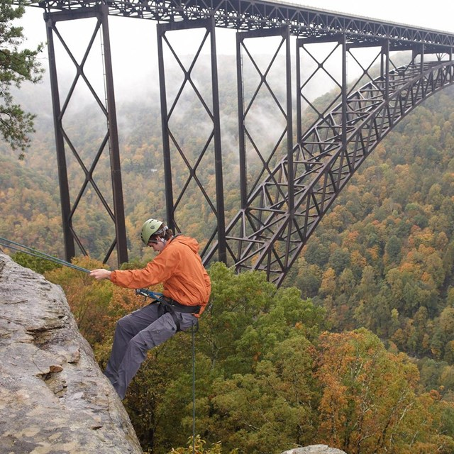 rock climber rappelling off cliff with bridge in background