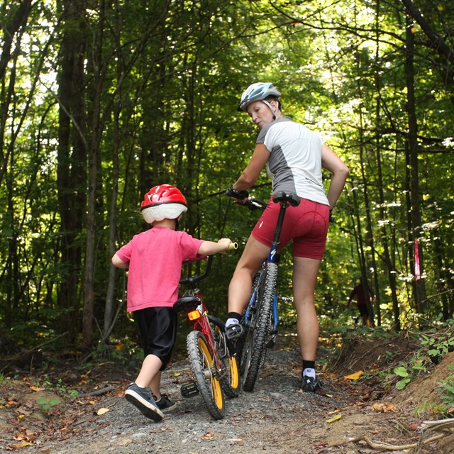 Mother and child mountain biking on a trail