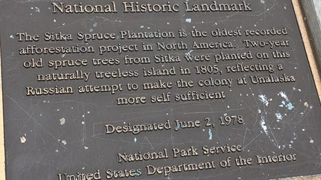 A bronze national historic landmark plaque for the Sitka Spruce Plantation, Unalaska