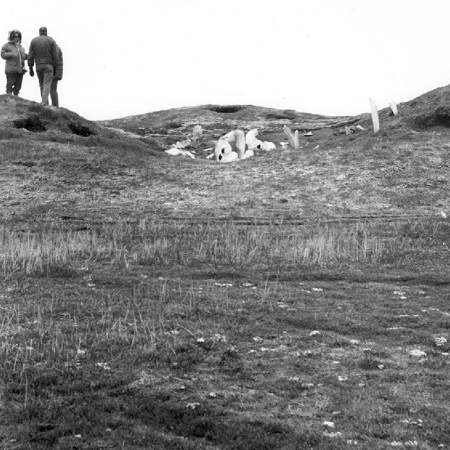 Historic photo of people standing on archaeological mounds with whale bone structure ruins.