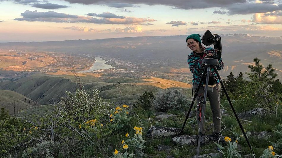 Sweeping valley view from atop a mountain shows a female scientist beside a tripod and CCD camera