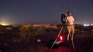 NPS scientist prepares cameras to measure sky glow conditions in the desert at night.