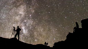 Silhouetted view of people stargazing against a vast backdrop of night sky