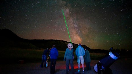 A park ranger uses a green laser to point out celestial features to visitors.