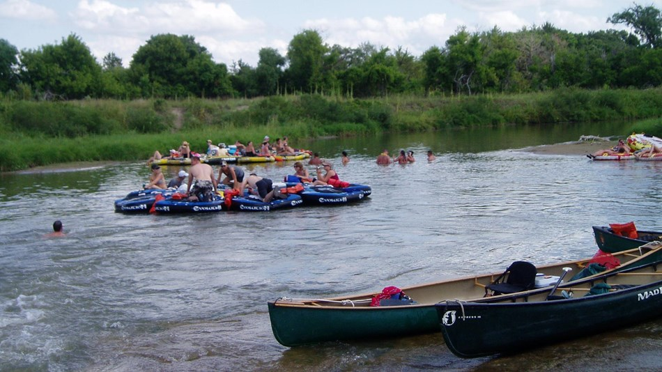 A group of tubes on a river with two canoes on the sandy shore.