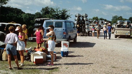 People and cars in a gravel parking lot with coolers and canoes.