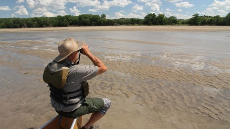 A man sits on the point of a canoe on a sandbar looking through binoculars.