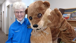 Volunteer standing with River Otter mascot.