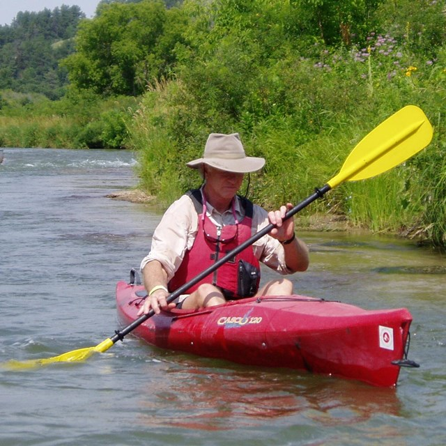 A kayaker in a red boat with a lifejacket and hat on
