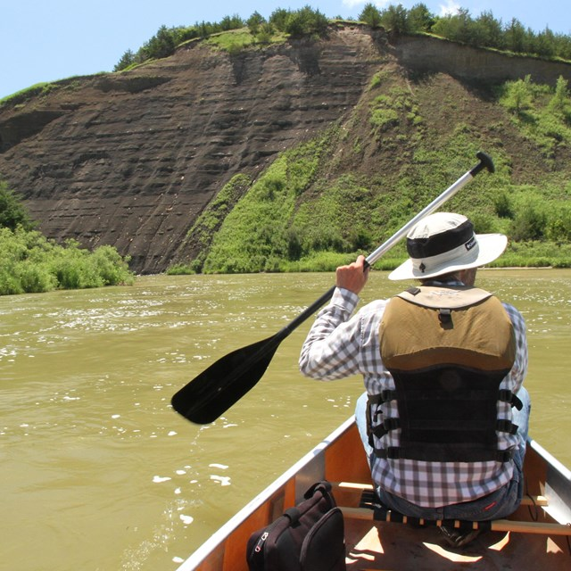 A canoer faces forward on a river, moving toward a dirt bluff