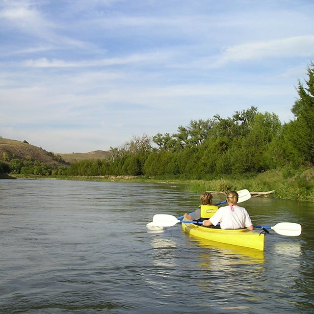 Two kayakers in a yellow boat on a calm river.