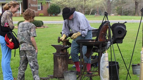 Visitors watch a blacksmith work.