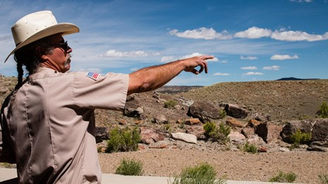 man in a cowboy hat points right while standing in a rocky terrain