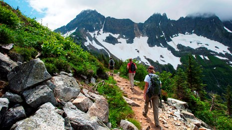 Three hikers travel along a dirt trail in the mountains.
