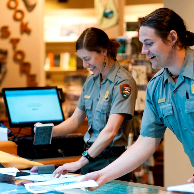 Two park rangers standing behind a visitor center desk.