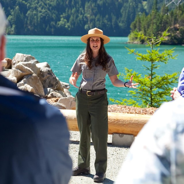 A park ranger addresses a crowd while standing in front of a blue lake.