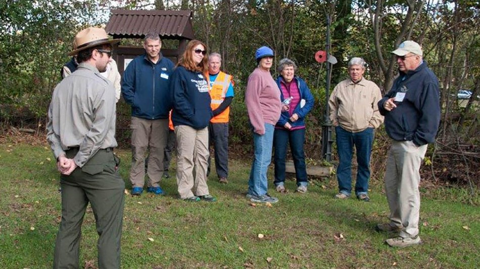A group gathers at a trailhead for a hike.