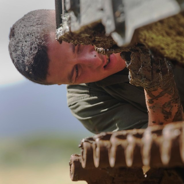 A marine solider scrapes invasive picklweed off an amphibious assault vehicle