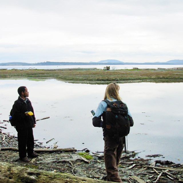 Two scientists with monitoring equipment beside a lagoon.