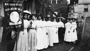 Black and white photo of Black women holding up suffrage signs