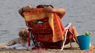 Dog laying next to a person in a chair on a beach