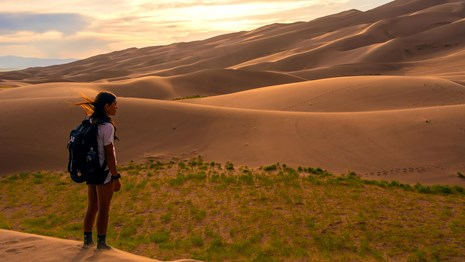 Kid standing near great sand dunes at dusk