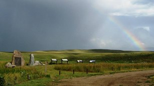 Rainbows over a grass field with interpretive panels