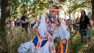 Native American dancer in tall grass with a crowd in the background