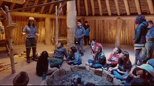Ranger talking to a group of kids seated inside an earth lodge