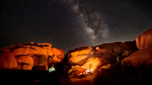 Campsite with tent and campfire in a desert under the Milky Way