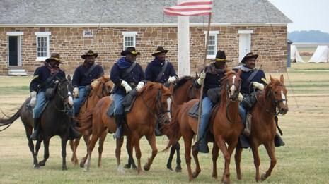 Line of Buffalo Soldier reenactors riding horses at a historic fort