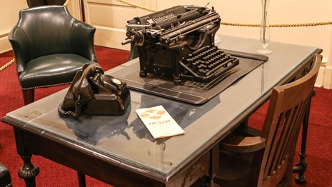 Desk with a typewriter and old telephone
