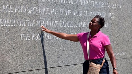 Visitor touching a quote on a memorial wall