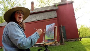 Painter painting a red barn on the other side of her canvas