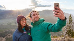 Two visitors taking a selfie in front of a canyon