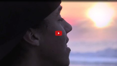 Screenshot from film of a person talking near the ocean