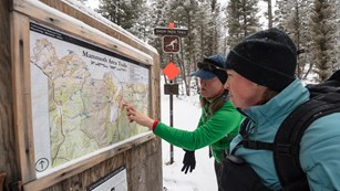 Visitors looking at a bulletin board map in a snow-covered forest