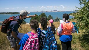 Guide pointing kids to a city skyline across a body of water