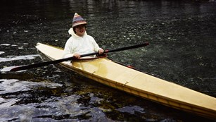 Historical color photo of a woman in a traditional kayak
