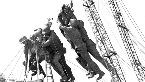 Historical black and white photo of statues of Marines lifted by a crane during construction