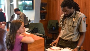 Park ranger going over a Junior Ranger book with a kid