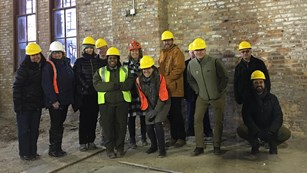 Group of people in hard hats next to a brick wall
